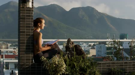 veranda : blond woman with long braid leans on roof terrace column and writes in diary against wonderful hills behind city