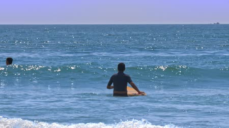 sports suit : guy surfer beginner goes into calm azure ocean holding yellow board waiting for wave