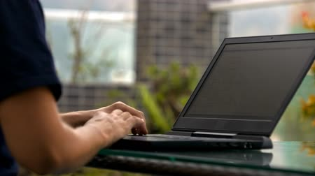 programista : closeup male programmer in dark clothes types on laptop creating a website in room with green plants Wideo
