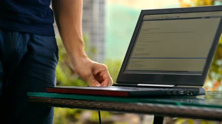 computer programmer : man programmer plugs remotely on a rooftop terrace Stock Footage