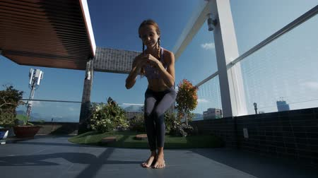blue braid : athletic young woman with plaits changes yoga poses on modern roof lounge