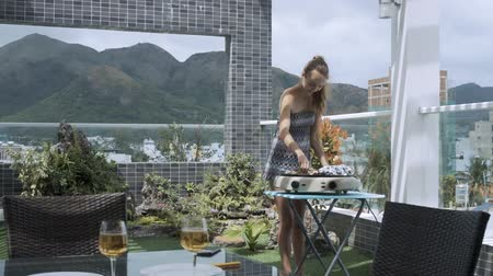 столовая гора : young pretty lady puts green onion with fresh meat on barbeque against large mountains on windy day