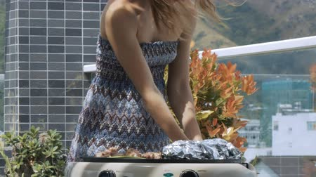 adega : closeup young woman in gray dress puts fresh onion on electric grill on roof terrace against pot plants Vídeos