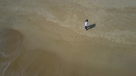 vakáció : amazing upper view newlyweds couple walking on boundless wet sand beach and rolling foamy ocean wave Stock mozgókép