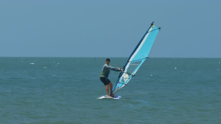 treinador : bald headed coach controls windsurfer beginner sliding on surfboard on turquoise ocean against distant horizon