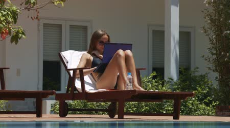 chaise longue : closeup nice girl lying on wood chaise longue near pool typing text on modern laptop against white house