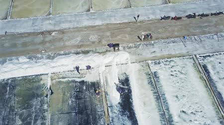 mořská voda : aerial panorama Asian workers gather evaporated salt with special shovels on large white plantations in rural area Dostupné videozáznamy