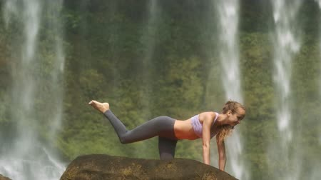 vietnã : side view attractive blonde girl doing fitness exercises on huge old green rock against waterfall