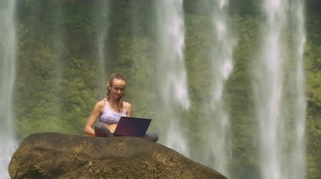 vietnã : pictorial close-up close-up of a lady sits in a lotus position on a rock and poses working at laptop against a foamy waterfall jets