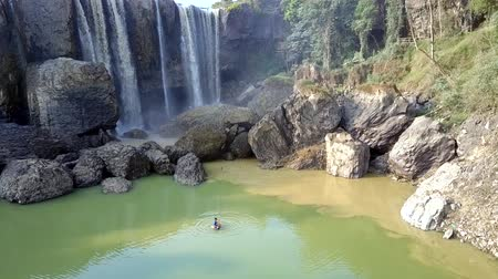 vietnami : asian boy swims in lake with rocks at waterfall