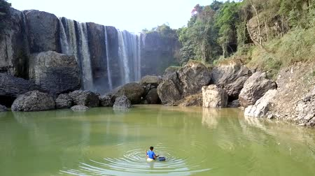 bao : local guy fishes in pond near waterfall