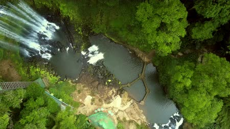 national park : flycam turns round above waterfall running into gorge