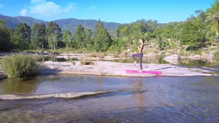 hatha : woman stands in yoga position against river with rapids