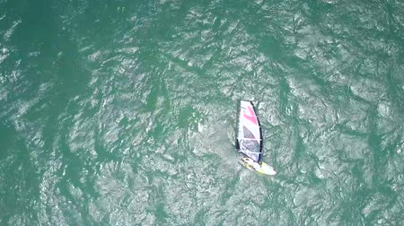 surfista : surfer holds sail swimming in turquoise ocean Stock Footage