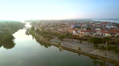 vietnami : light sky and trees reflect in calm Hoi An channel