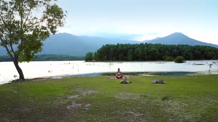 oposto : distant view girl changes yoga pose on lake bank