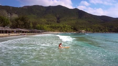 доска для серфинга : girl goes into ocean to do surfing against hilly landscape