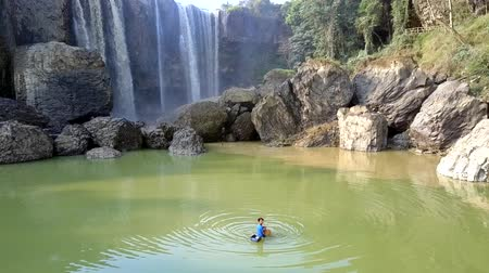 lifebuoy : foamy waterfall streams from height boy fishes in pond