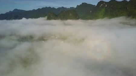 seyahat : sun rays light fog over valley and form round rainbow Stok Video