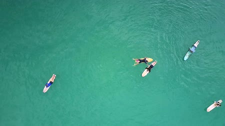 невероятный : upper view surfers lie resting on surfboards among ocean