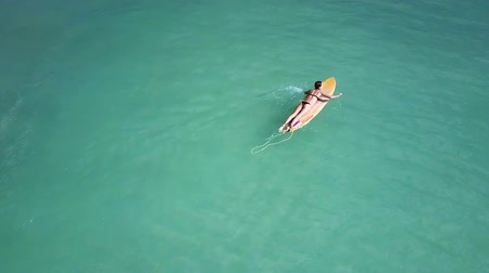 remoção : lone girl surfer swims on board and guy appears