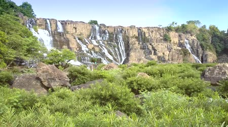 perseguição : motion to Pongour waterfall above river brushwoods