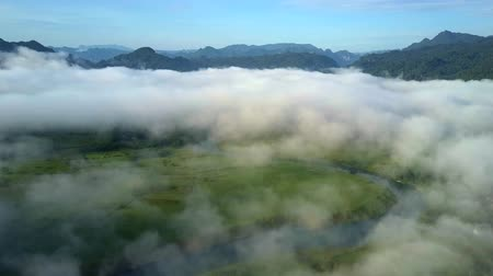 protrude : clouds cover valley with river and bizarre hills against sky Stock Footage