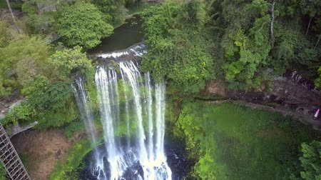 virgin forest : drone goes down to waterfall among lush jungle