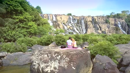 zadek : couple sits on rock among river rapids by waterfall Dostupné videozáznamy