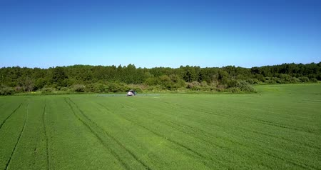 postřikovač : green field with machinery against forest under blue sky