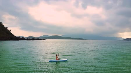 sucção : woman swims on paddleboard to islands on horizon