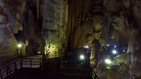 gruta : tourist walk on dark bridge by lamps line in cave