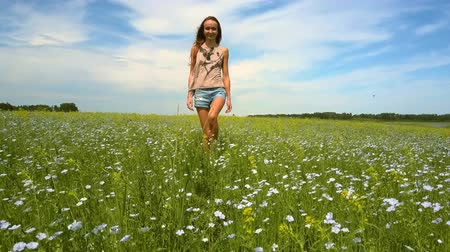 trigo sarraceno : nice smiling girl walks on blossoming buckwheat field