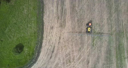 baton : tractor sprayer moves on harvested field along forest