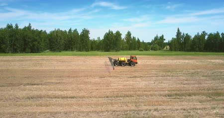 recentemente : tractor trailer for spraying fertilizers moves on harvested field