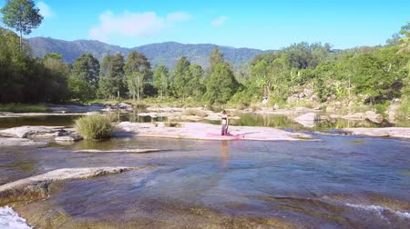 hatha : girl doing yoga on stone against mountain river