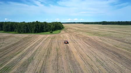 recentemente : flight over tractor driving on large harvested field