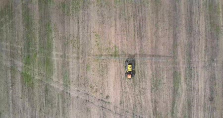 recentemente : drone hangs above agricultural vehicle on harvested field