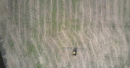 recentemente : aerial view tractor turns back on harvested field by forest Vídeos