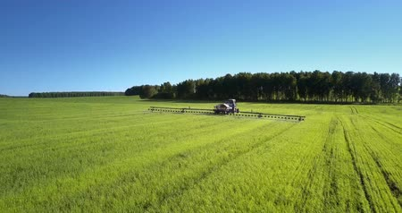 окропляет : tractor field sprayer with chemicals operates near wood