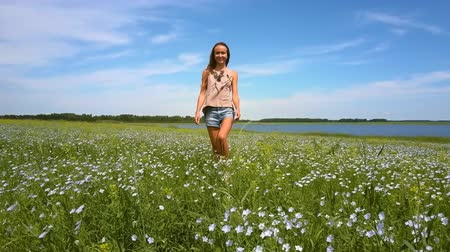 brim : butterflies fly around girl walking on buckwheat field