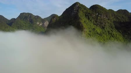 tourist silhouette : drone flies above fog to protruding illuminated mountains Stock Footage