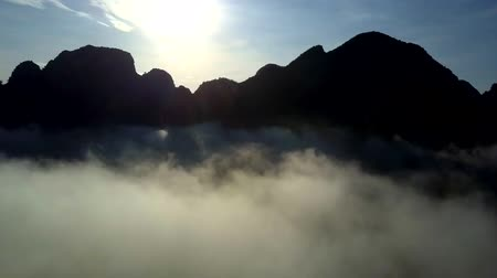 thick : hills silhouettes among foggy clouds against sunrising sky
