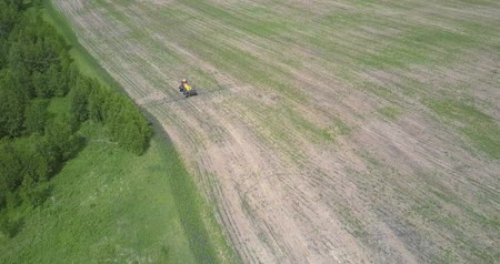 recentemente : aerial view tractor moves on harvested field among woods Vídeos