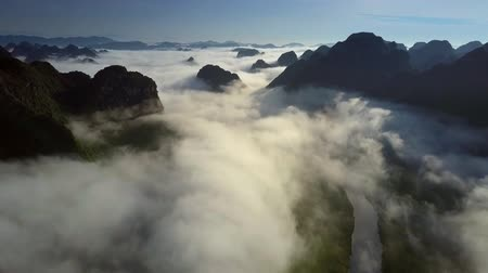 protrude : aerial view endless mountains protrude from clouds