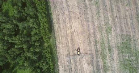 recentemente : aerial view tractor drives on harvested field along forest Vídeos