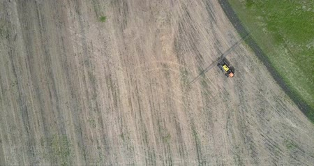 recentemente : bird eye flight tractor turns on harvested field around lawn side Vídeos