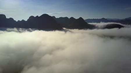 protrude : endless aerial panorama mountains protrude from white fog Stock Footage