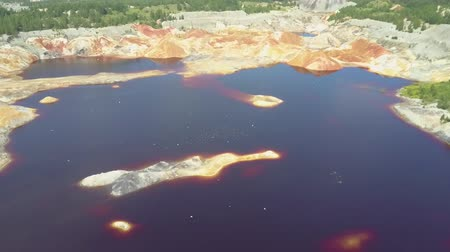 dark island : flycam moves close to blue pond water on clay pit with birds Stock Footage
