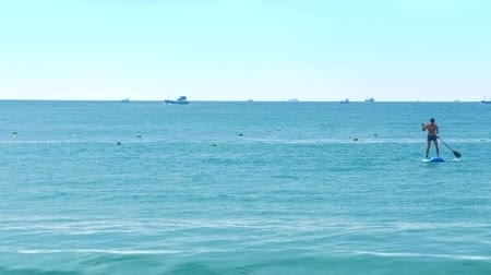 surfer paradise : man learns to paddle board against ocean with boats